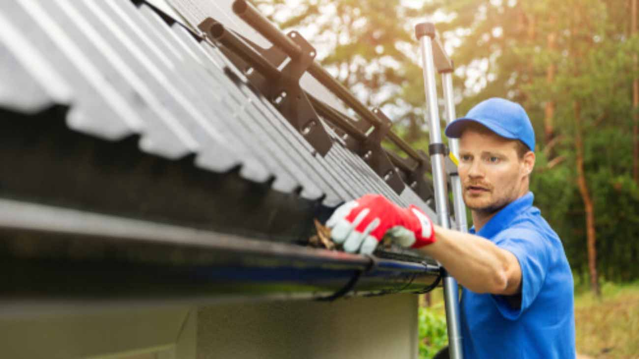 Worker,Cleaning,House,Gutter,From,Leaves,And,Dirt